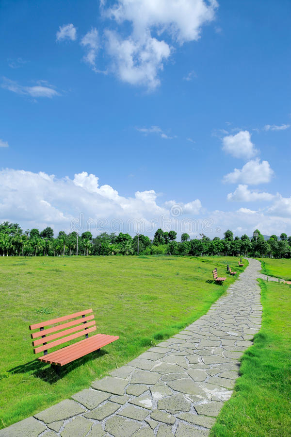 Garden path, public green space. Garden path,green lawn,chairs with a path royalty free stock image