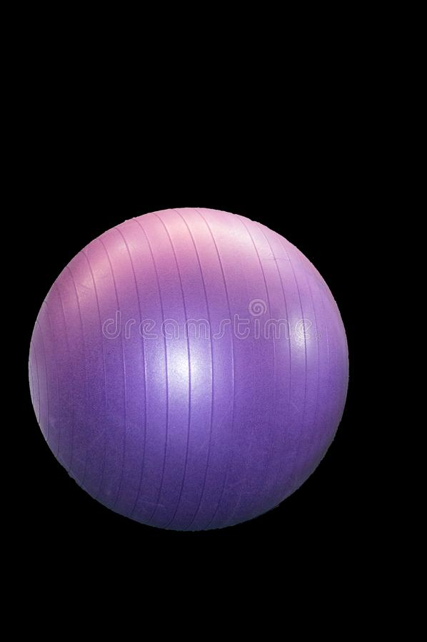 Large purple fitness ball isolated on black background by clipping, vertical frame royalty free stock images
