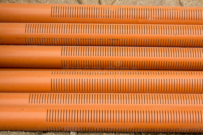 Large PVC pipe. Large diameter orange PVC pipe into the ground before laying royalty free stock photography
