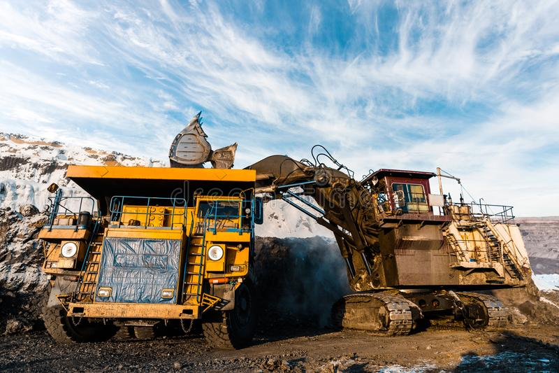 Large quarry dump truck. Loading the rock in dumper. Loading coal into body truck. Production useful minerals. Mining stock photo
