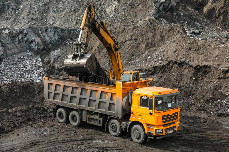 Large quarry dump truck. Loading the rock in dumper. Loading coal into body truck. Production useful minerals. Mining. Large quarry dump truck. Loading the rock stock photos