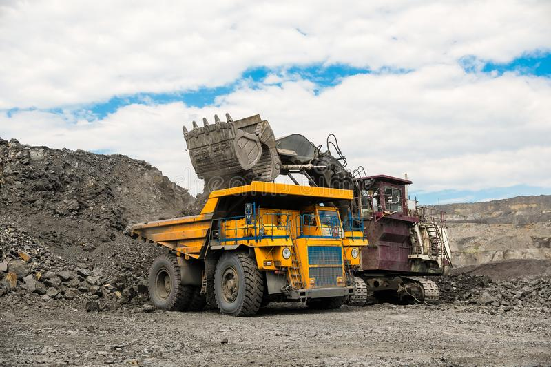 Large quarry dump truck. Loading the rock in dumper. Loading coal into body truck. Production useful minerals. Mining. Large quarry dump truck. Loading the rock stock photography