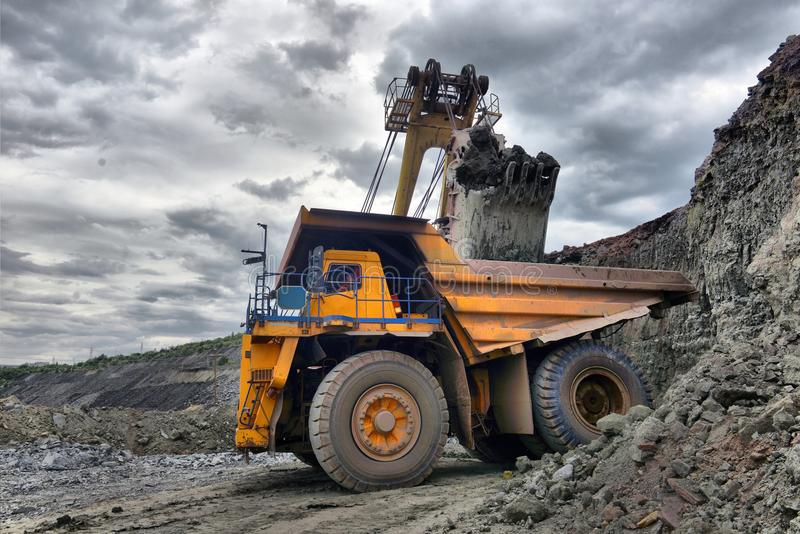 Large quarry dump truck. Loading the rock in the dumper. Loading. Coal into body work truck. Mining truck mining machinery, to transport coal from open-pit royalty free stock photos