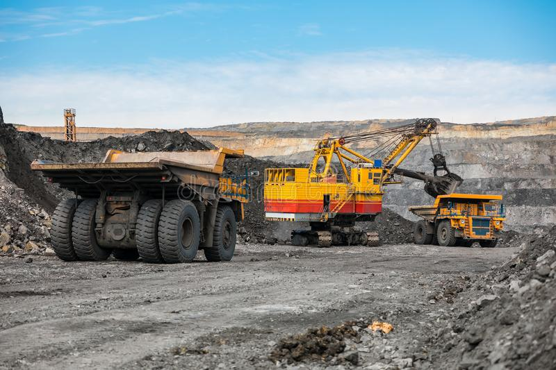 Large quarry dump truck. Loading the rock in dumper. Loading coal into body truck. Production useful minerals. Mining. Large quarry dump truck. Loading the rock royalty free stock photos