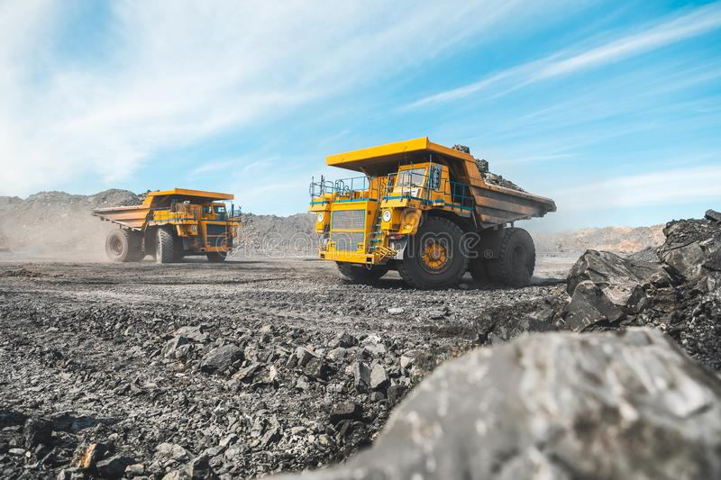 Large quarry dump truck. Loading the rock in dumper. Loading coal into body truck. Production useful minerals. Mining stock images