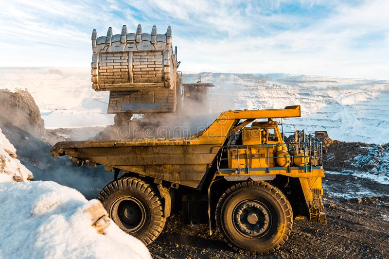 Large quarry dump truck. Loading the rock in dumper. Loading coal into body truck. Production useful minerals. Mining stock photos