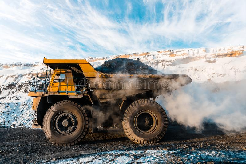 Large quarry dump truck. Loading the rock in dumper. Loading coal into body truck. Production useful minerals. Mining stock image