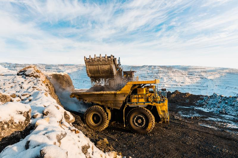 Large quarry dump truck. Loading the rock in dumper. Loading coal into body truck. Production useful minerals. Mining. Large quarry dump truck. Loading the rock stock photo