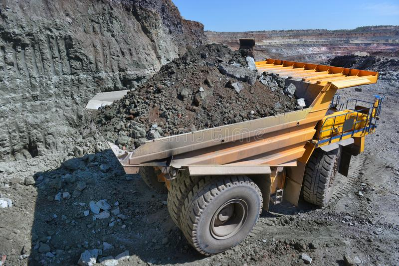 Large quarry dump truck. Loading the rock in the dumper. Loading. Coal into body work truck. Mining truck mining machinery, to transport coal from open-pit stock photography