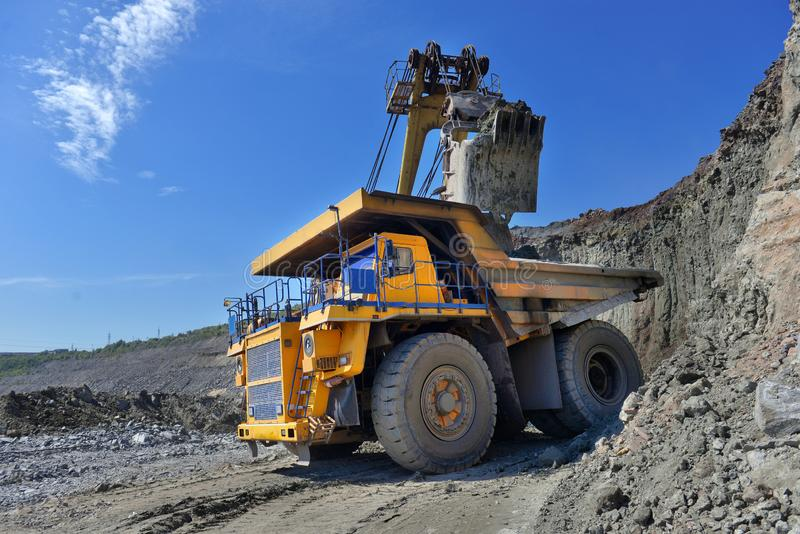 Large quarry dump truck. Loading the rock in the dumper. Loading. Coal into body work truck. Mining truck mining machinery, to transport coal from open-pit royalty free stock photography