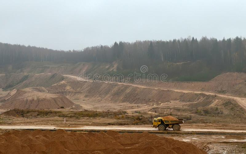 Large quarry dump truck. View of the large sand pit. Production useful minerals. royalty free stock image