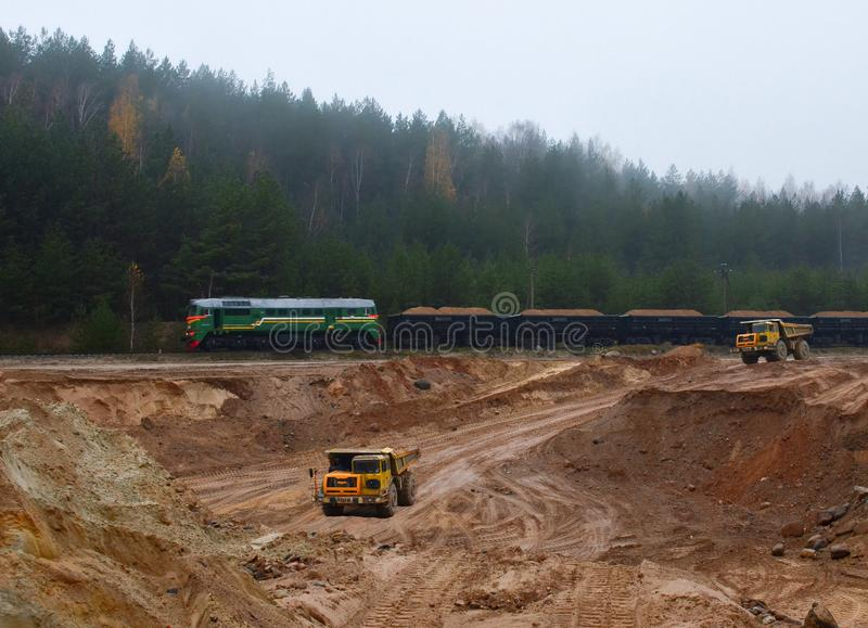 Large quarry dump truck. View of the large sand pit. Production useful minerals. Loading the rock. stock photography
