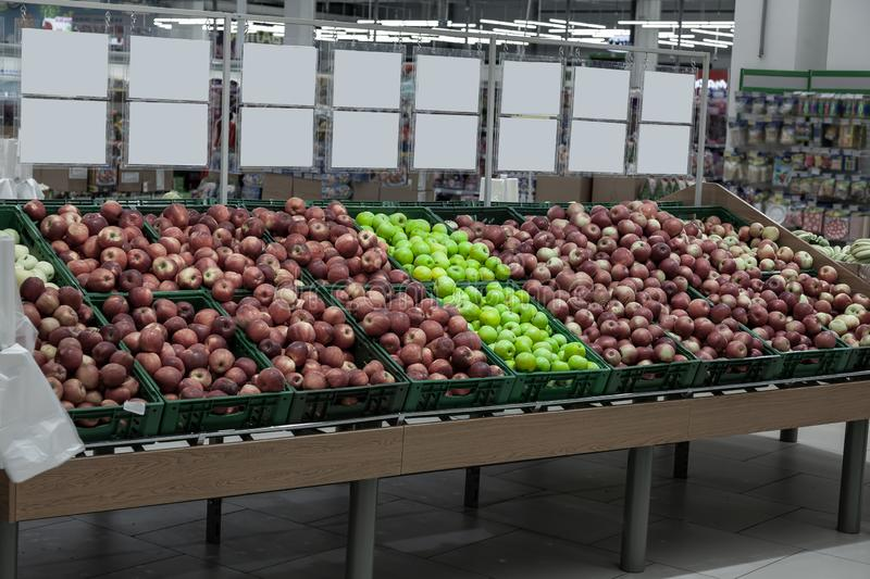 A large rack with baskets with different types of apples in the fruit department of the shopping center. Fresh and healthy foods f royalty free stock photos