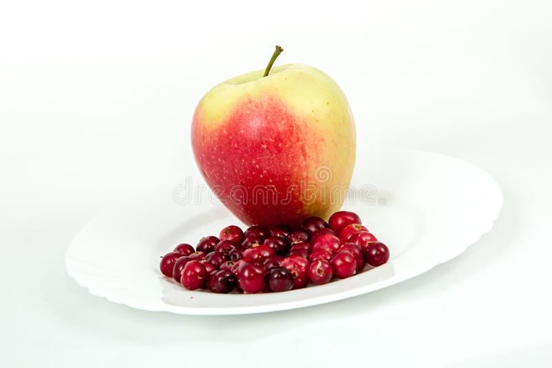 A large red Apple on a white plate with cranberries stock photography