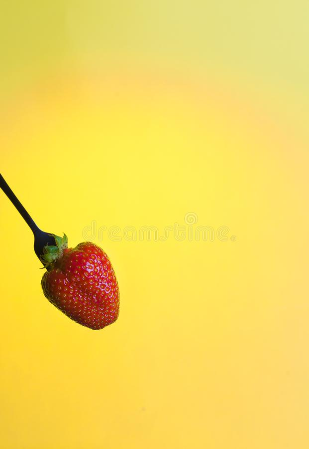Large red strawberry on bright yellow warm background stock image