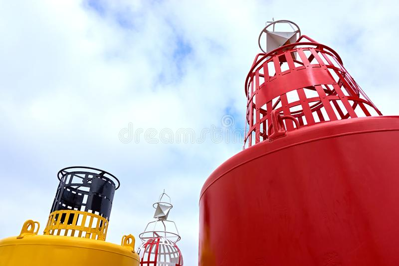 Large red and yellow buoy. Against a blue cloudy sky with copy space royalty free stock images