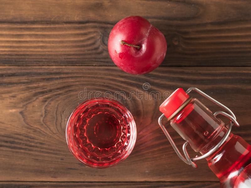 Large ripe plum and plum liqueur on a wooden table. Flat lay. Large ripe plum and plum liqueur on a wooden table. Homemade alcoholic drink made from berries royalty free stock photos