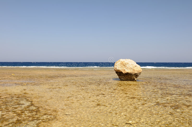 Large rock on beach stock image