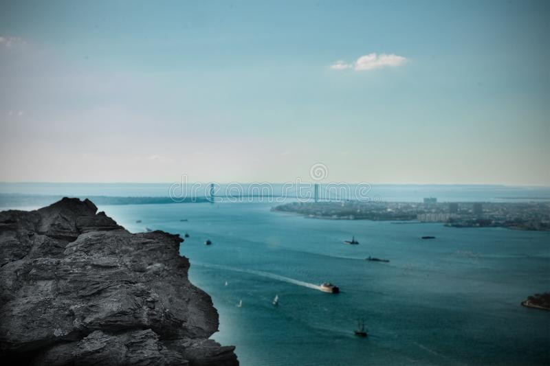 Large rock overlooking harbour with bridge royalty free illustration