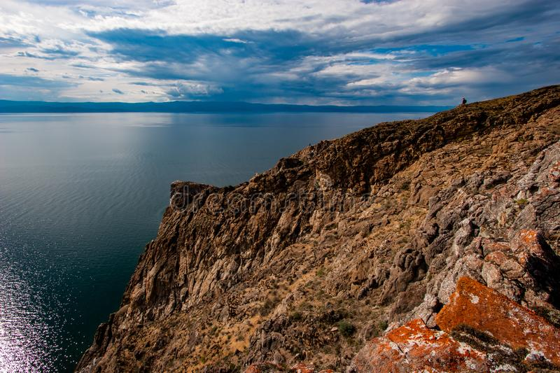 Large rock with red stones on Lake Baikal. The sky in the clouds. On the water ripples. stock images