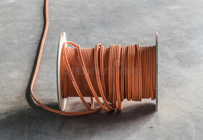 Large roll of communications cable on concrete floor stock images