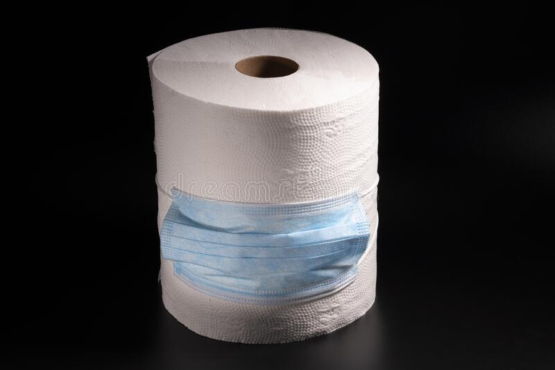 A large roll of toilet paper or paper towels with a medical mask on a black background. Close-up royalty free stock photos