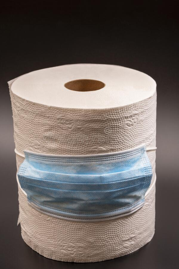 A large roll of toilet paper or paper towels with a medical mask on a black background. Close-up royalty free stock images