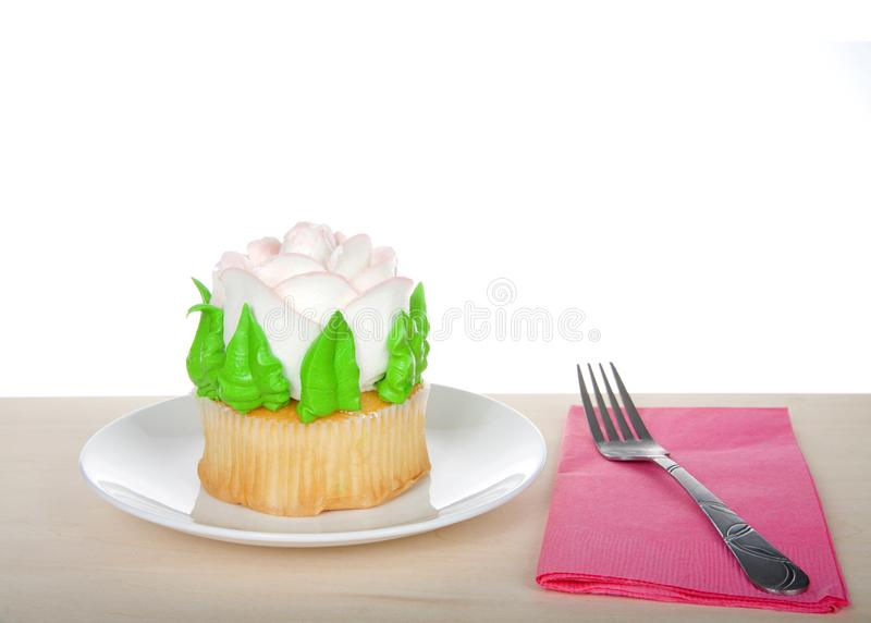 Large rose cup cake on table with napkin and fork. Large cup cake with giant frosting rose sitting on white plate on wood table, pink napkin with fork. Simple royalty free stock images