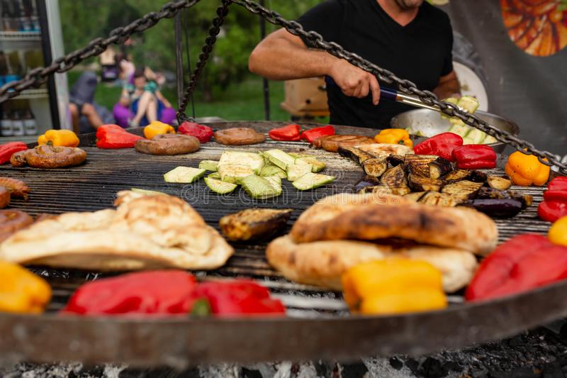 A large round grill on the coals in which grilled color vegetables and fresh meat sausages are cooked. Food and equipment for royalty free stock photos