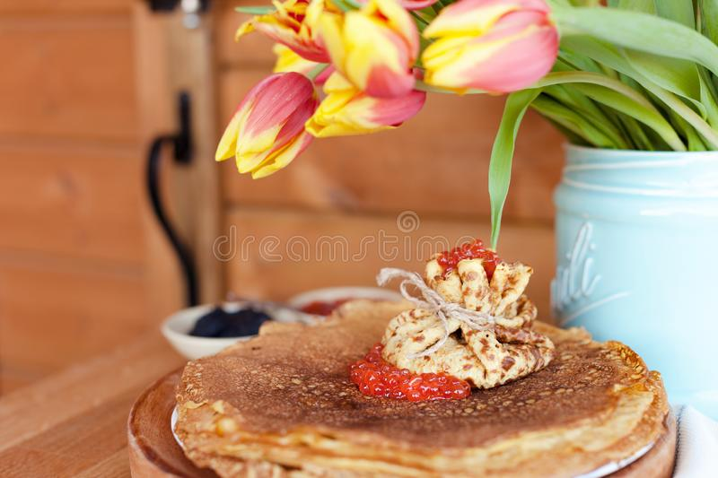 Large round pancakes with red and black caviar. Envelopes from pancakes with filling. A bouquet of fresh spring tulbpans on the stock photo