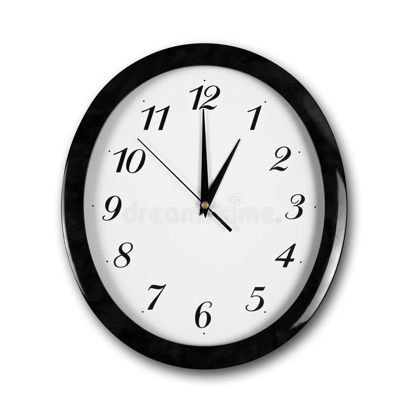 Large round white wall clock with black frame. The hands point to 1 o`clock. Close up. Isolated on white background.  royalty free stock images