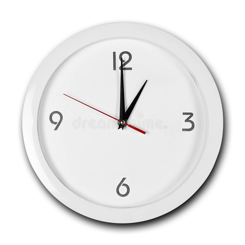 Large round white wall clock with white frame. The hands point to 1 o`clock. Close up. Isolated on white background.  royalty free stock photography