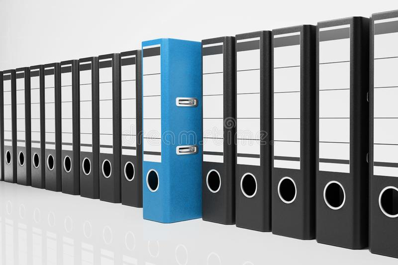 Large row of black office folders with one blue binder, conceptual archive 3D Illustration stock illustration