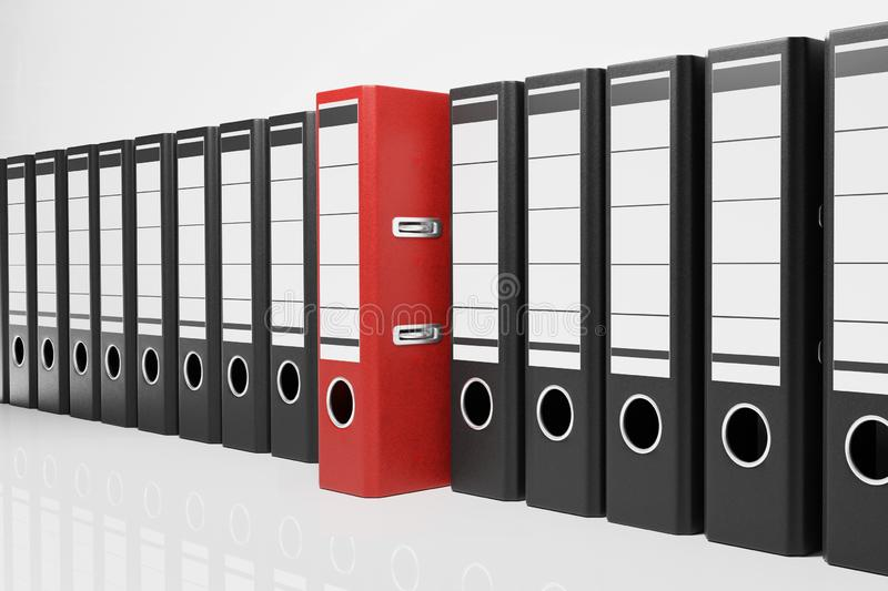 Large row of black office folders with one red binder, conceptual archive 3D Illustration stock illustration