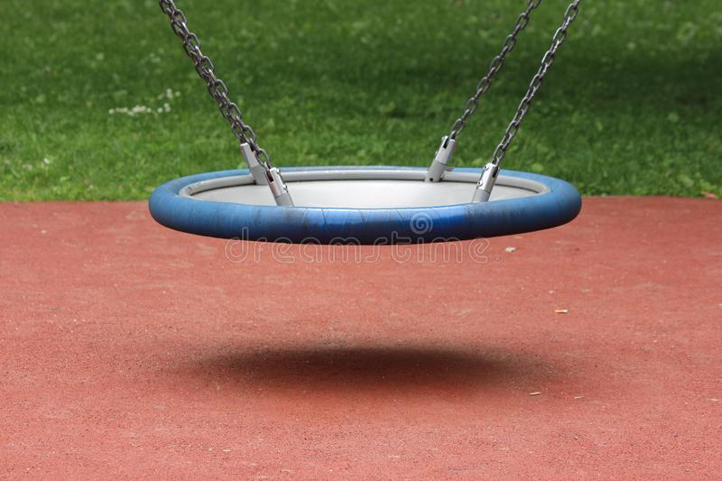 Large rubber swing with elastic middle suspended in air with four strong chains over playground sand in local park surrounded with. Uncut grass on warm sunny royalty free stock photography