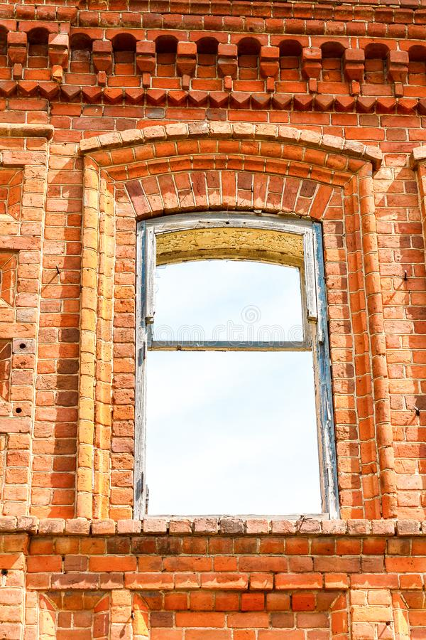 A large ruined ancient house of red brick against a blue sky with white clouds. A big ruined ancient house of red brick against a blue sky with white clouds royalty free stock photos