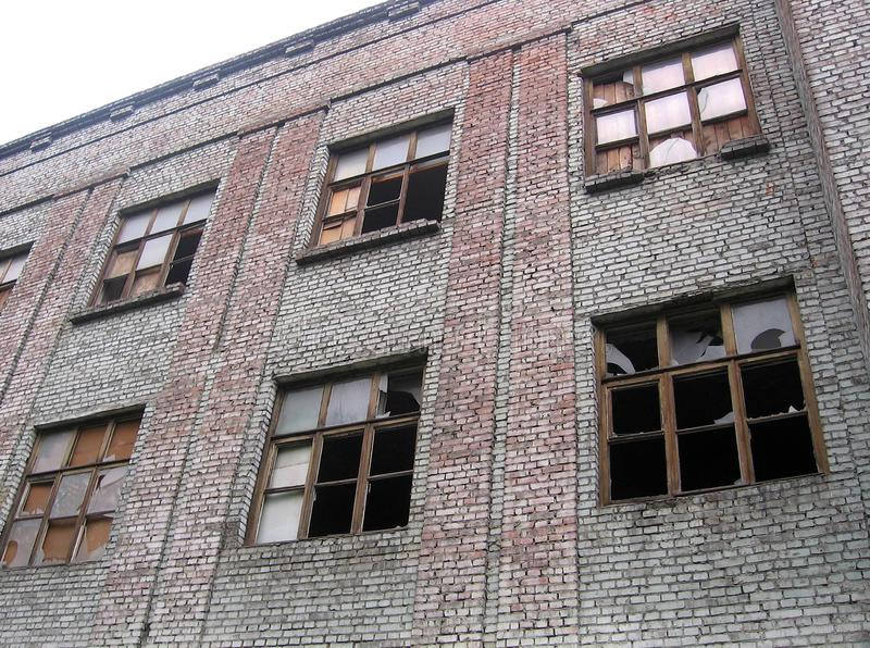 A large ruined brick building with broken Windows forgotten junk stock photos
