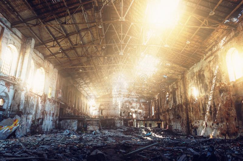 Large ruined and demolished abandoned factory hangar or warehouse in sunlight, post apocalyptic disaster concept. Toned stock photos