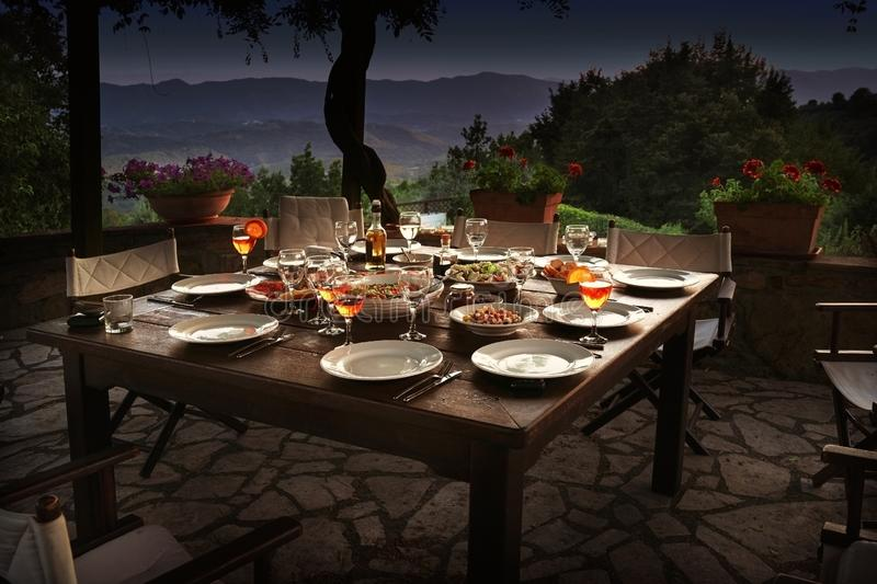 Large rustic table on a garden terrace prepared for a dinner party at night stock images