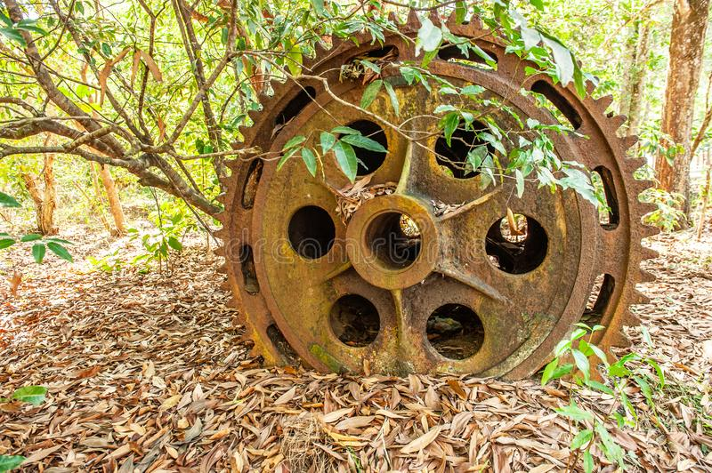 Large rusty gear of Tin Dredge in the deserted tin mine. Dry leaves fall on the ground, tropical forest backgrounds. Thai Mueang, Phang Nga, South Thailand royalty free stock images