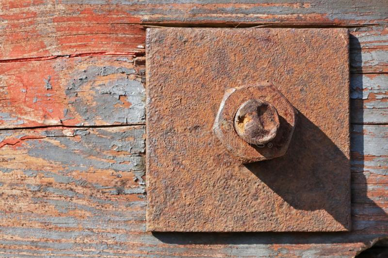 Large rusty nut holds wood  aged painted planks together royalty free stock images