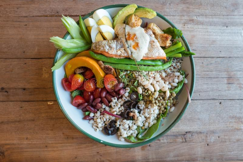 Large salad bowl of vegetables beans tomato pumpkin avocado and eggs mixed with grilled salmon on wooden table. royalty free stock photography