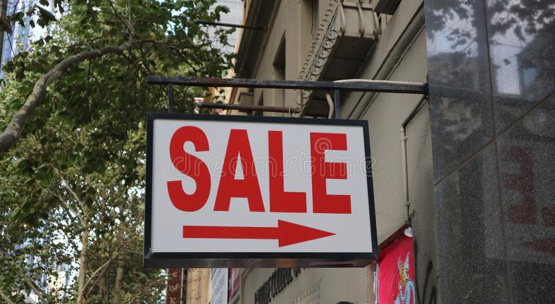 A `Sale` sign in a commercial precinct. A large `Sale` sign hung in an urban retail street, featuring an arrow to the right stock photo