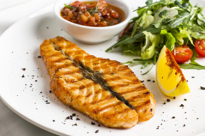 The large salmon steak red fish on the grill with lemon, sauce and greens stock photos