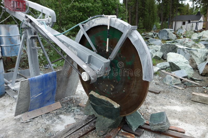 A large saw used to cut jade mined in canada. Jade being cut with a heavy-duty saw just off the cassiar highwat stock images