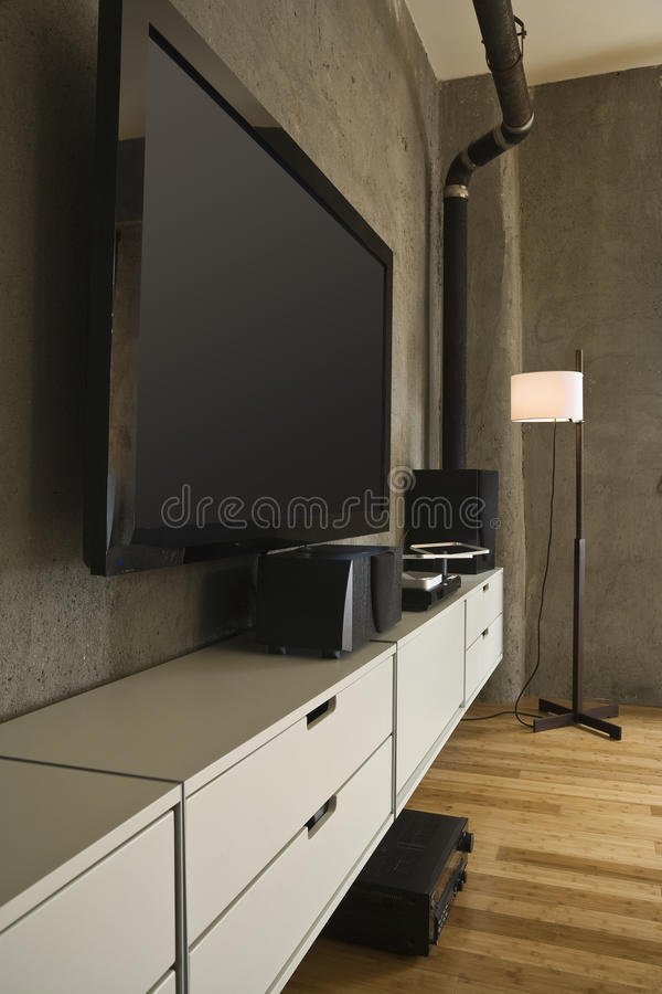 Large Screen TV and Entertainment Center. Large flat panel television and entertainment center in a modern loft. Vertical shot royalty free stock photos
