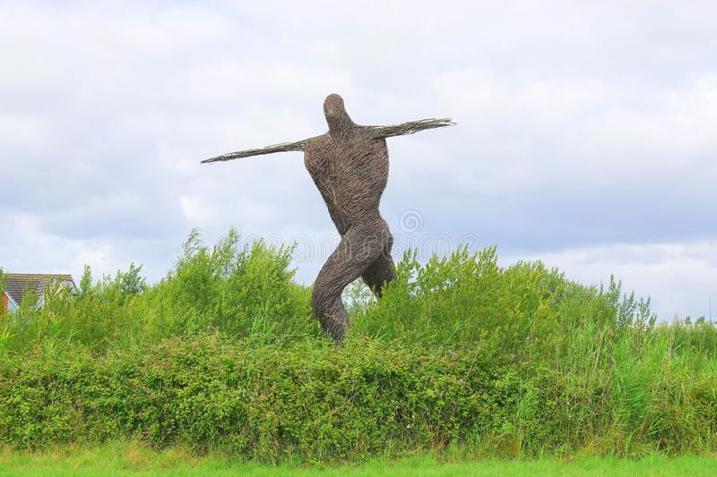 Willow sculpture of walking man. Large sculpture of the Willow Man alongside the M5 Motorway in Bridgwater in Somerset, England stock image