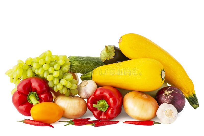 Eggplant zucchini pink tomato garlic red onion Golden grapes with bell and chili peppers pink tomato on white background royalty free stock photos