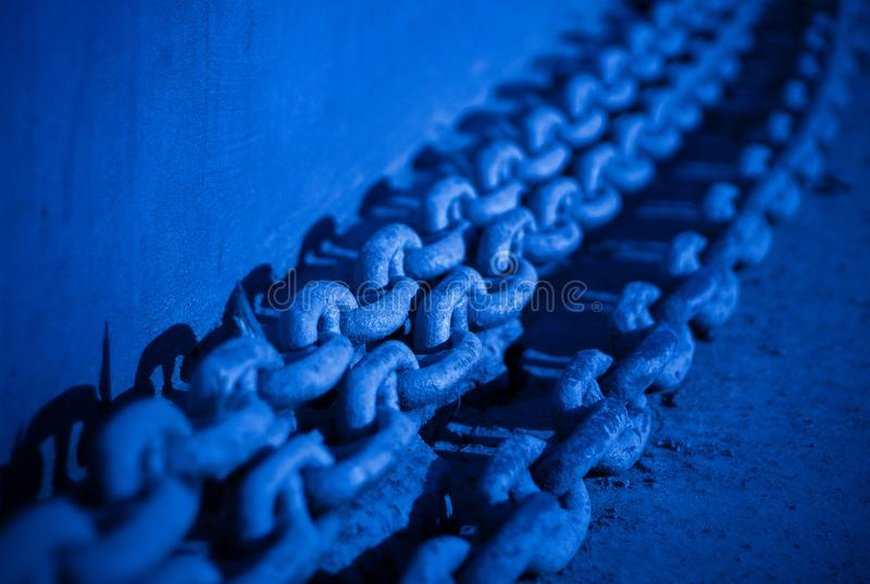 Large ship chains close-up. Large ship chains closeup tinted in classic blue color, symbol of strength and power stock photo