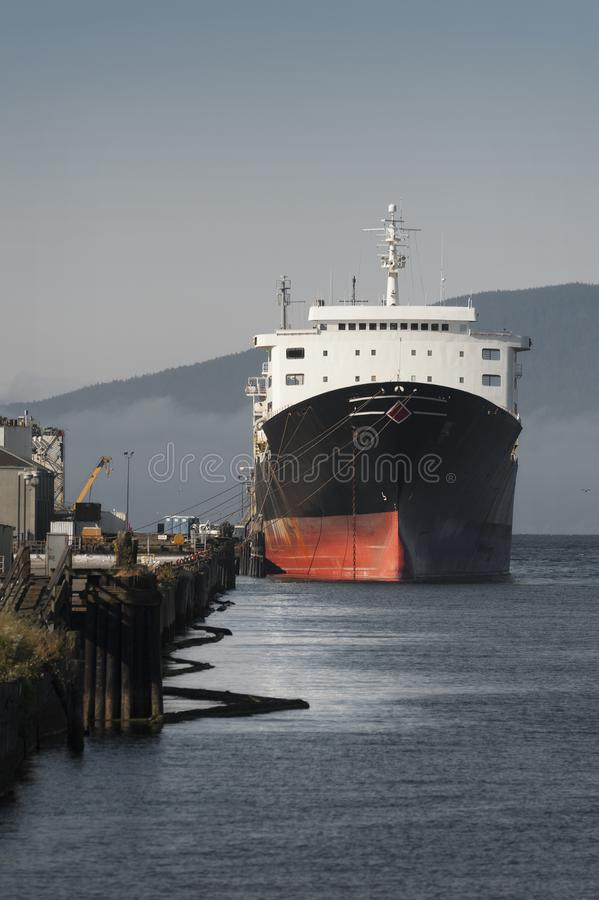 Large Ship Docked in Bellingham, Washington. A commercial freighter tied up to a dock on the waterfront of Bellingham, Washington, waiting to be loaded with stock images